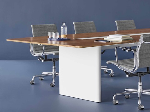 A meeting space featuring an Axon Table with a white base and wood top. Four Eames Aluminum Group Chairs featuring a grey textile surround the table.