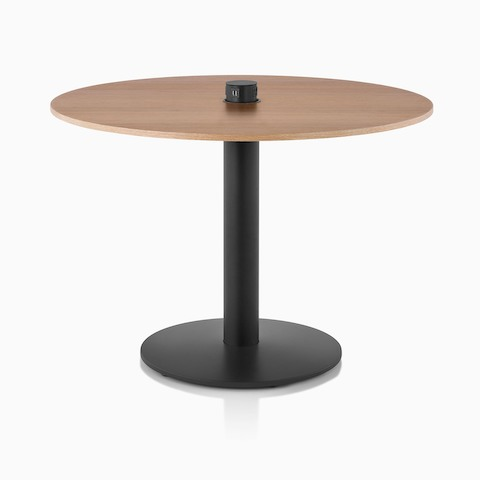 A round Axon Conference Table featuring a black base and a natural oak top.