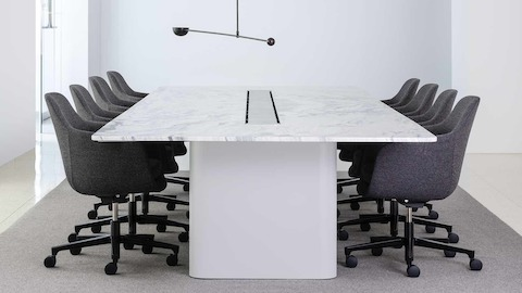 Side view of a rectangular Axon conference table with a marble top surrounded by gray Saiba office chairs.