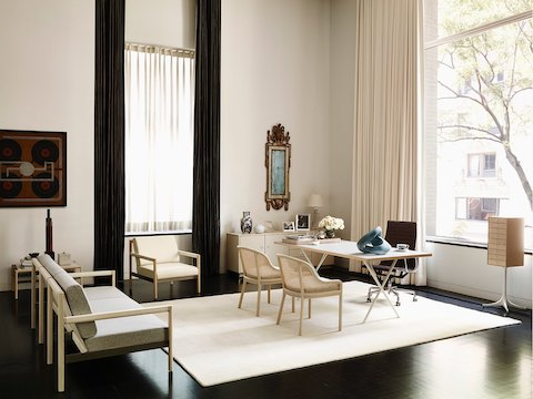 An upscale home office featuring large windows, a Brabo sofa and chair, a Nelson X-Leg Table, and a Nelson Miniature Chest.