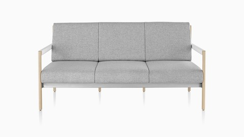 A light gray Brabo sofa with wood legs and black arms, viewed from the side.