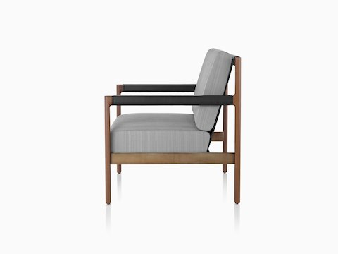 Profile view of a gray Brabo lounge chair with wood legs and black arms.