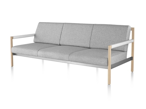 An angled view of a light gray Brabo sofa with wood legs and white arms.