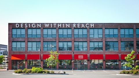 An outdoor photograph during a sunny day of a Design Within Reach studio housed in a brick loft-style building.