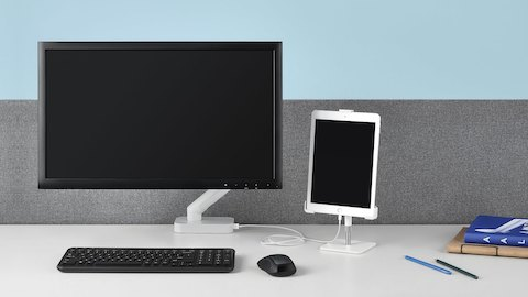 A computer monitor and small tablet sit on a white desk with gray divider, with keyboard, mouse, and a stack of notebooks. Select to learn more about CBS.