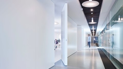 A line of movable white walls to the left and glass paneled walls to the right line a long hallway with two men walking through. Select to learn more about Maars.
