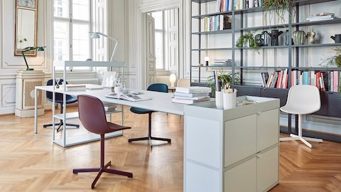 A modern white desk is stacked with a few books, task lamp, and accessories. Surrounding it are burgundy, blue, and white chairs and a dark gray metal bookshelf along a wall, with intricate white woodwork and herringbone wood floors. Select to learn more about HAY.