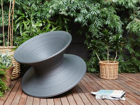 A black Magis Spun Chair on an outdoor deck surrounded by foliage.