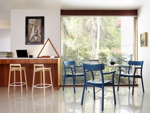 Two Mattiazzi Branca Stools with a light wood finish join three blue Mattiazzi Chiaro Chairs in a casual work setting.