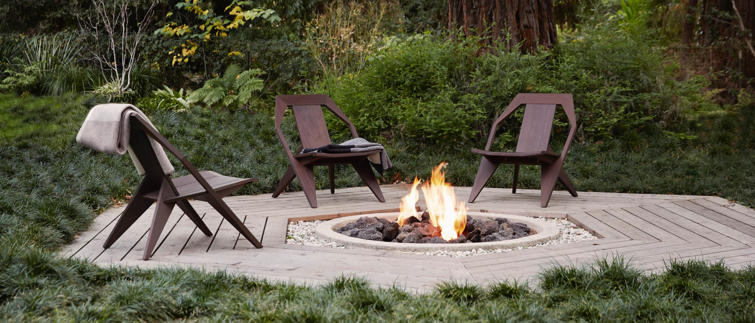 Three Mattiazzi Medici outdoor chairs on a hexagonal deck with a firepit in the middle.