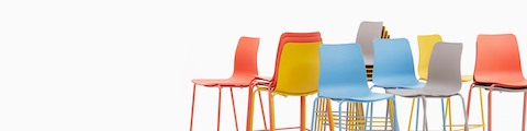Multiple Polly barstools from naughtone in shades of red, yellow, blue, and gray.