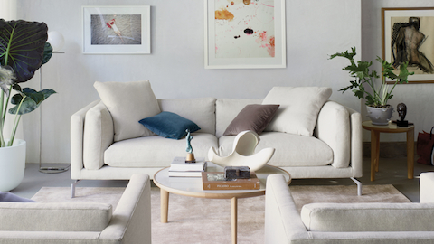 A sofa with cream-colored fabric upholstery, flanked by side tables and plants, facing two armchairs upholstered in the same cream-colored fabric.