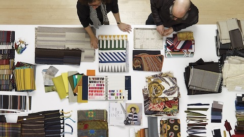 An overhead view of two people examining a variety of fabric and material swatches on a white table.