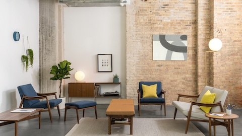 An open lounge with Nemshoff armchairs and sofas near coffee tables and side tables, and art on exposed brick walls.