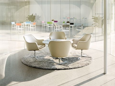 Four white leather Bumper lounge chairs surround a round table.