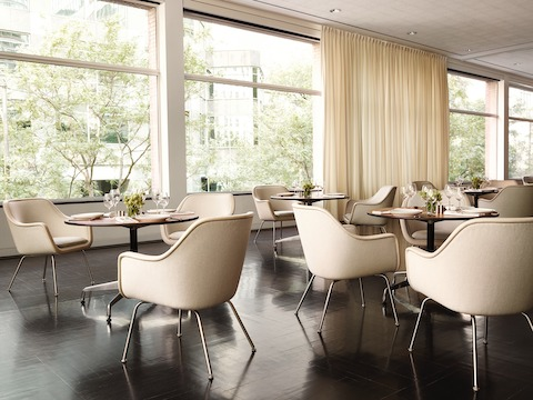 Dining environment featuring four-leg Bumper Chairs in tan fabric.