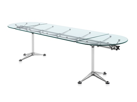 An oval Burdick table with a glass top, white leg columns, and aluminum bases, viewed from a 45-degree angle.