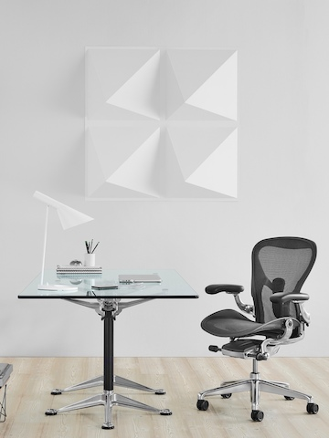 A square Burdick table with a glass top, used as a desk and complemented by a black Aeron office chair.