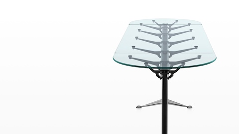 An oval Burdick table with a glass top, black leg columns, and aluminum bases, viewed from the narrow end.