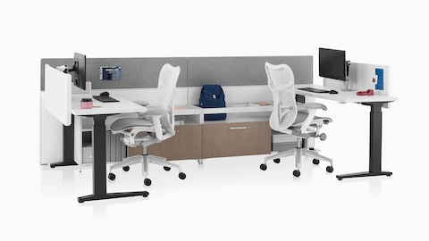 A white Canvas Channel workstation with light wood lower storage, grey screens, Motia height-adjustable tables, and light grey Aeron office chairs.