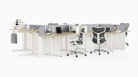 White Canvas Channel workstations with light wood height-adjustable tables, grey screens, and dark grey Mirra 2 office chairs.