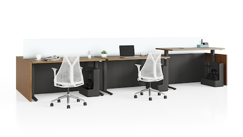 Canvas Channel workstations with dark wood height-adjustable tables, glass screens, and white Sayl office chairs.