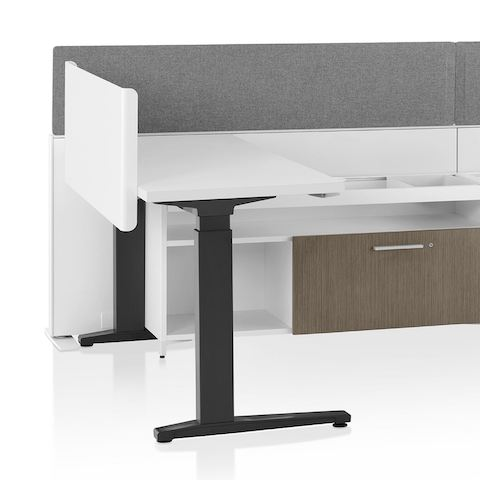 A close-up image of a Canvas Channel workstation with lower storage, grey fabric screens, and Motia height-adjustable table.