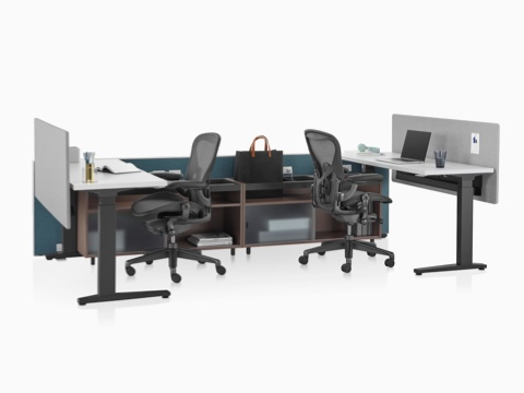 A Canvas Channel setting in dark green with lower storage, Motia height-adjustable tables, and black Aeron office chairs.