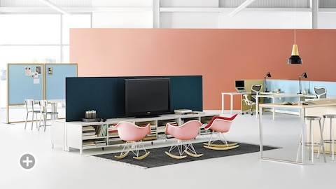 An office setting with Canvas Dock, Canvas Storage with blue screens, and pink Eames molded plastic rocking chairs. Select to go to the Impromptu Meeting Spaces page within the Canvas Lookbook.