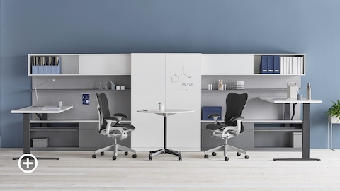 A shared Canvas Private Office with white and gray storage, one standing desk at seated height and one standing desk at standing height, and black Mirra 2 office chairs. Select to go to the Impromptu Meeting Spaces page within the Canvas Lookbook.