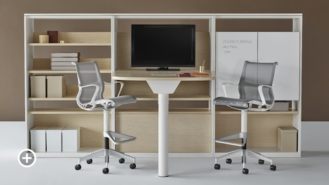 A Canvas Group display wall with a standing height collaboration table and gray Setu office stools. Select to go to the Impromptu Meeting Spaces page within the Canvas Lookbook.