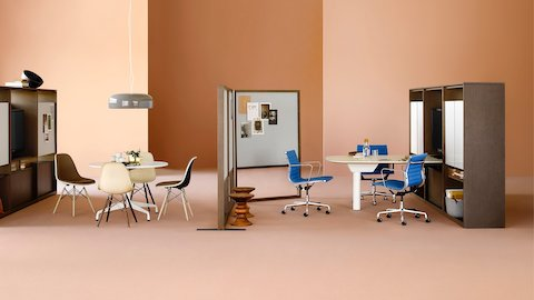 A Canvas Group display wall with a display, writable surfaces, blue Eames office chairs, and a nearby lounge setting.