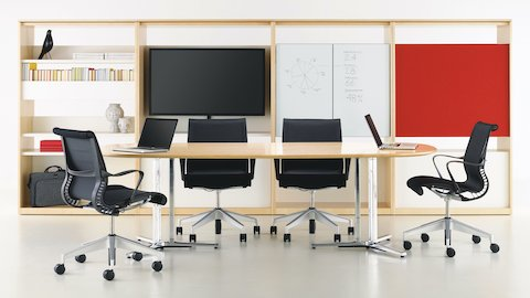 A Canvas Group display wall with storage, a display, and writable surfaces near a collaborative space.