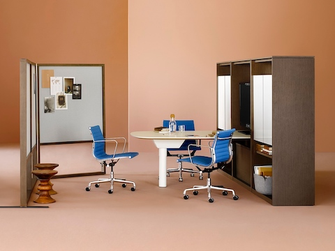 A Canvas Group display wall with a display, writable surfaces, blue Eames office chairs, and freestanding screens.