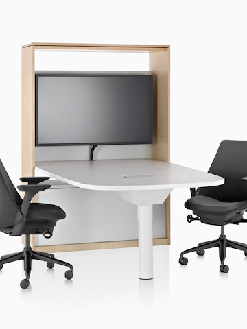 Two black Sayl office chairs on either side of a table and media cabinet. Select to go to the Canvas Group-Based product page.