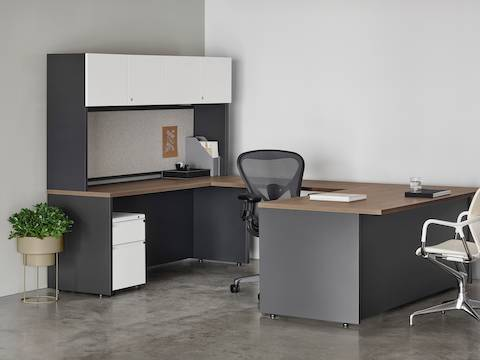 A Canvas Metal Desk with white overhead Canvas Storage, gray back panel, and a black Aeron Chair.