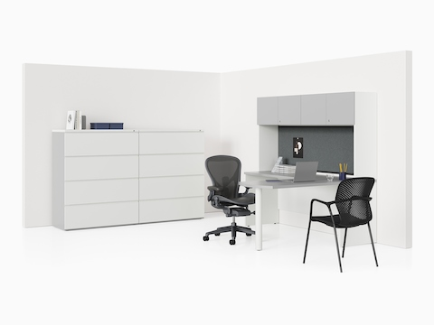 A dark gray Canvas Metal Desk in a private office with white storage, dark wood surfaces, and an Aeron Chair.