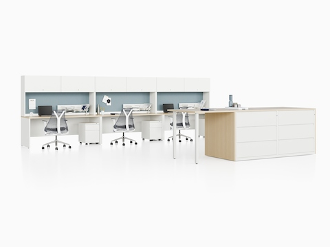 Three white Canvas Metal Desk workstations with light blue tack boards and a storage unit.