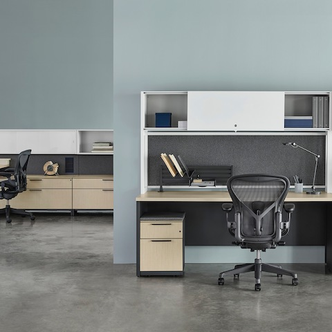 A Canvas Metal Desk with white upper storage, gray fabric back panels, and light wood surfaces with another workstation in the background.