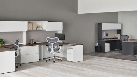 A pair of white Canvas Metal Desks with storage hutches, gray Mirra 2 Chairs, and a dark grey private office in the background.