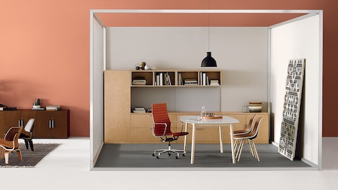 A private office using Canvas Office Landscape with an orange upholstered Eames Aluminum Group chair and two brown Eames Shell Chairs.