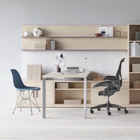 A Canvas Private Office desk with light wood storage, upper shelves, black Aeron office chair, and blue Eames Molded Plastic side chair.