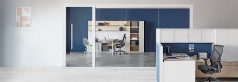 A Canvas Wall workstation with blue panels and white overhead storage and a Canvas Private Office setting in the background.