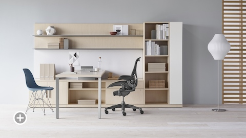 A Canvas Private Office with light wood storage, upper shelves, black Aeron office chair, and a blue Eames Molded Plastic side chair. Select to go to the Private Workspaces page within the Canvas Lookbook.