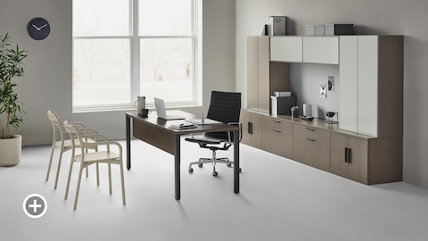A traditional Canvas Private Office with dark wood and glass storage, a black Eames Aluminum Group office chair, and two light wood Branca side chairs. Select to go to the Private Workspaces page within the Canvas Lookbook.
