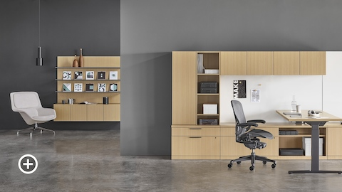 A Canvas Private Office with light wood storage, a standing desk positioned at sitting height, a black Aeron office chair, and a light gray Striad lounge chair. Select to go to the Private Workspaces page within the Canvas Lookbook.