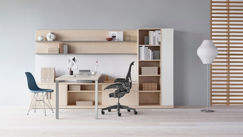 A Canvas Private Office with light wood storage, upper shelves, a black Aeron office chair, and a blue Eames Molded Plastic side chair.