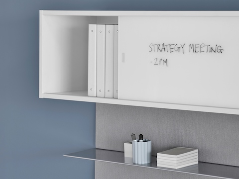A close-up image of white, writable overhead storage with an aluminum shelf underneath.