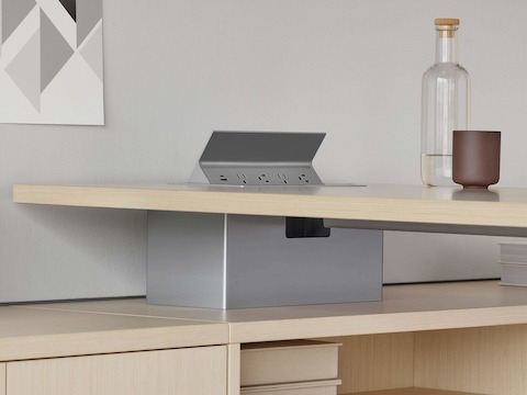 A grey power access unit in the surface of a light wood Canvas Private Office desk.
