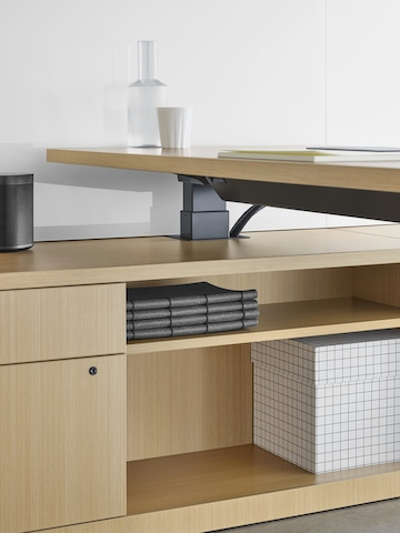 A light wood, height-adjustable desk integrated into a light wood storage unit.